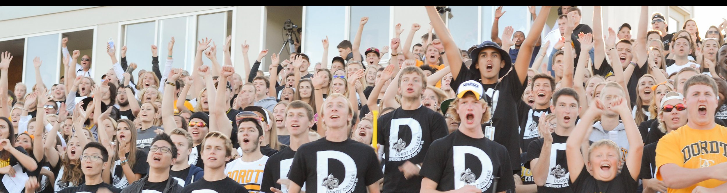 Dordt students raise their arms and cheers in the bleachers at a football game.