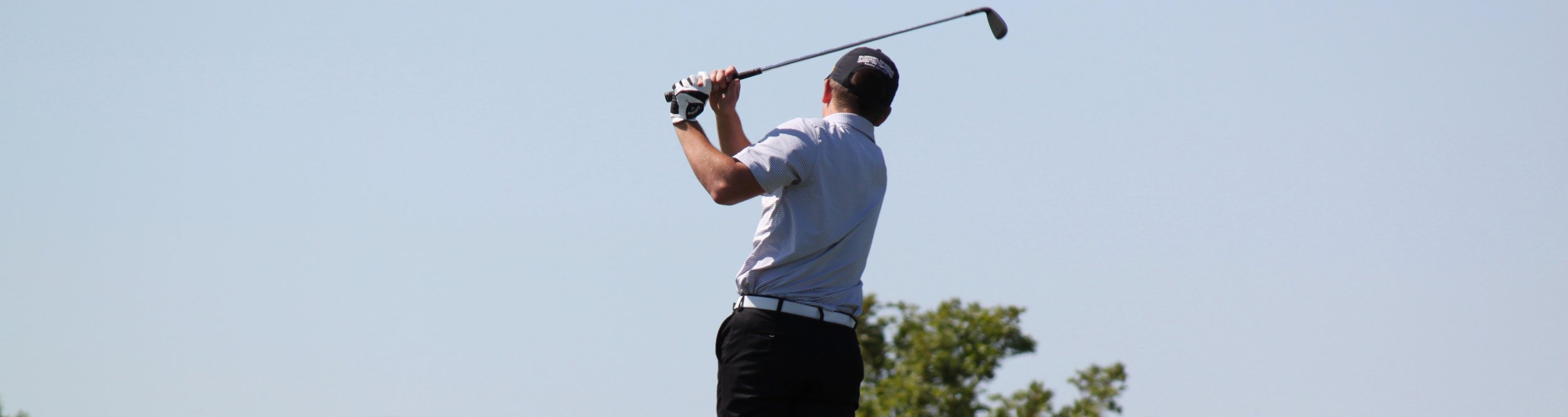 A male golf player raises his club.