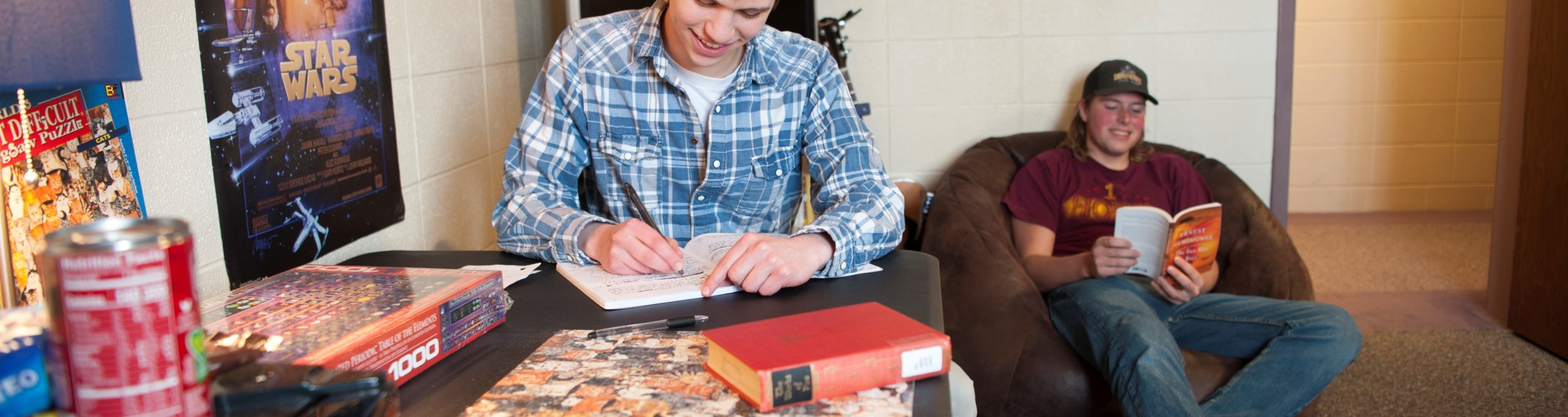 A male student writing in a journal in his dorm room.