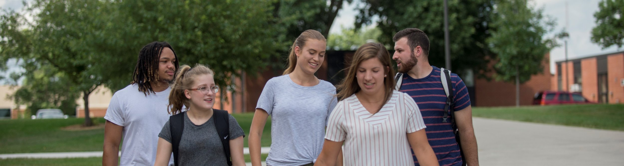 A group of students walk on the sidewalk together.