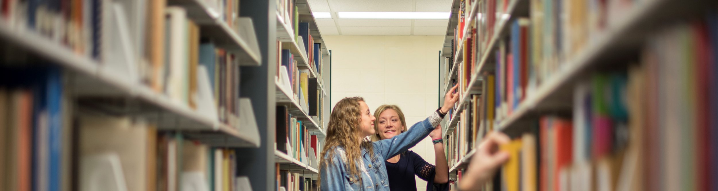 Two students look at the shelves in the Hulst Library.