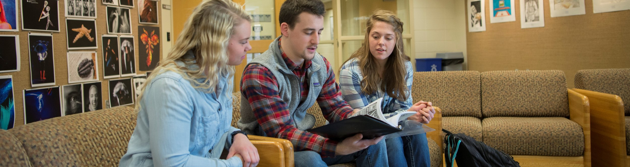 A student flips through a book, showing it to two other students.
