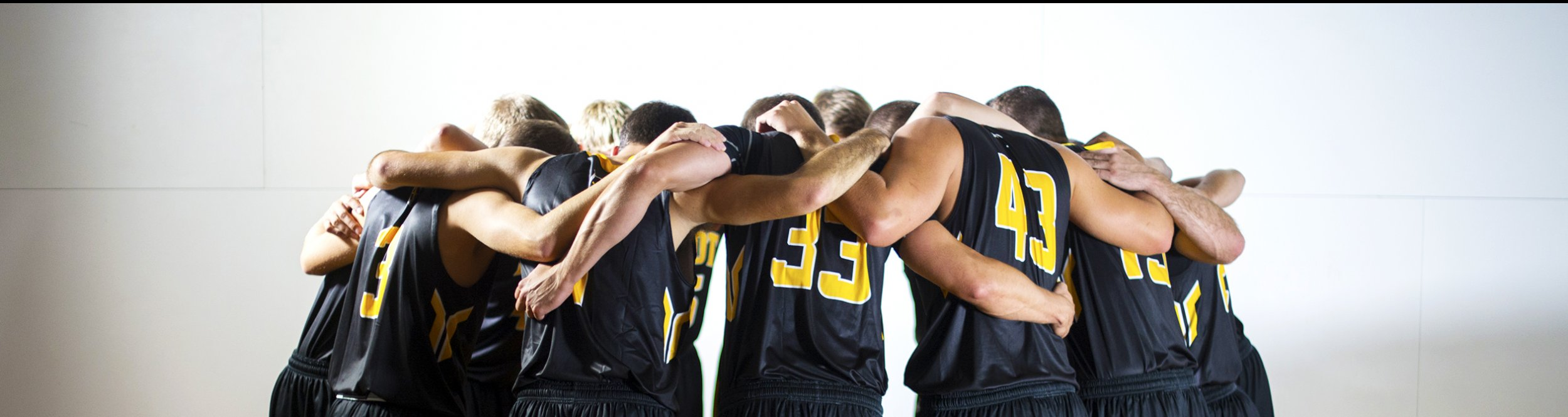 Men's basketball players join together in a huddle.