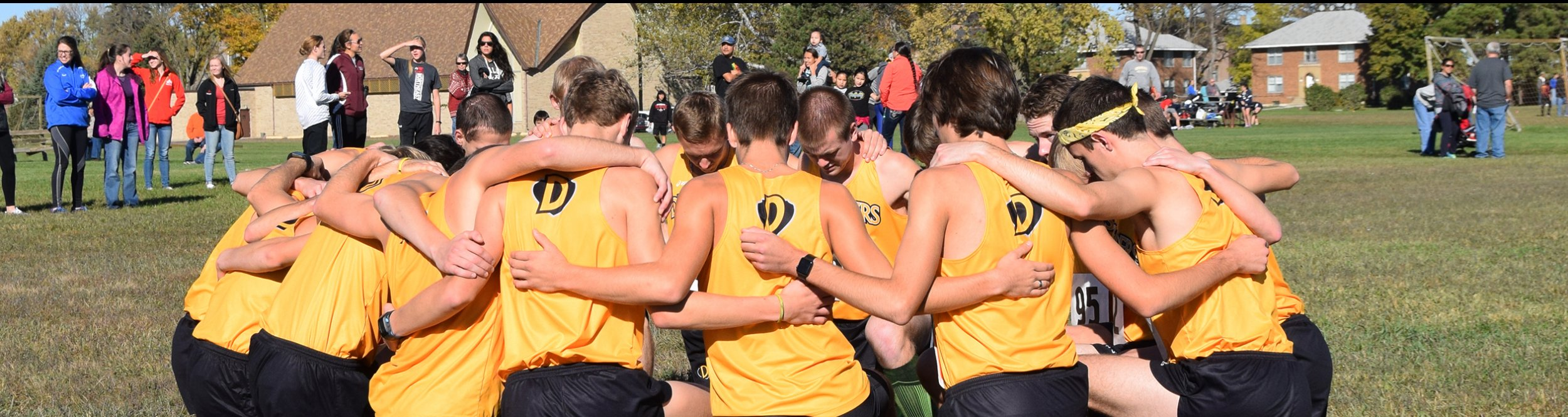 The men's cross country team huddles together.