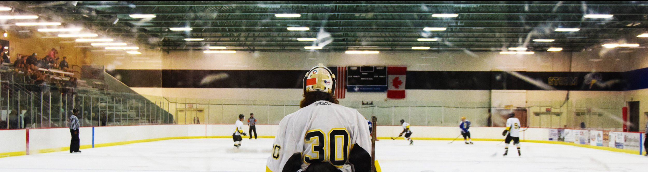 A men's hockey player looks at the entire ice rink.