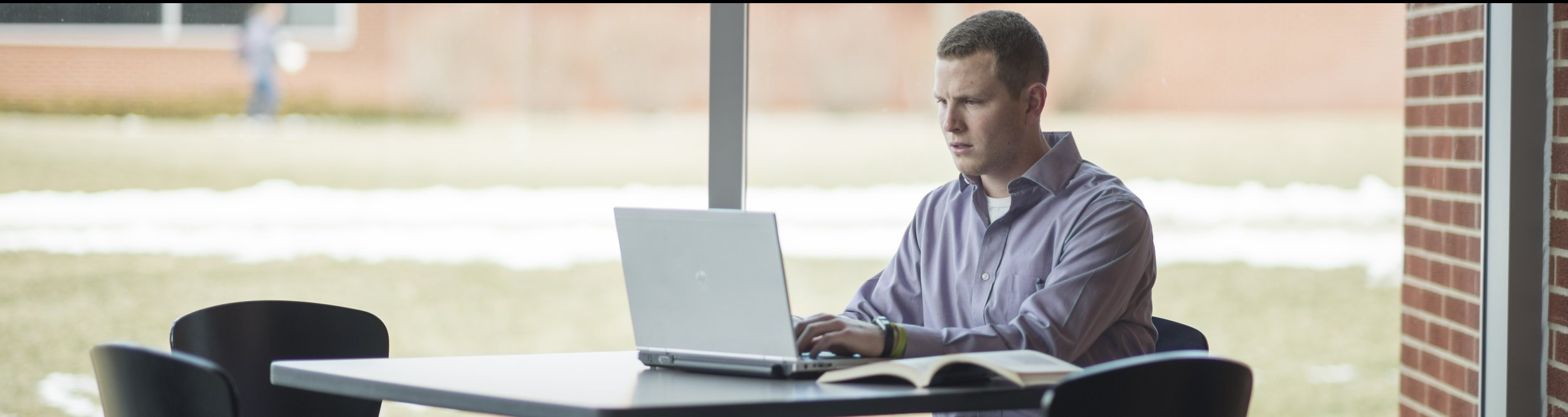 A male student types on his laptop.