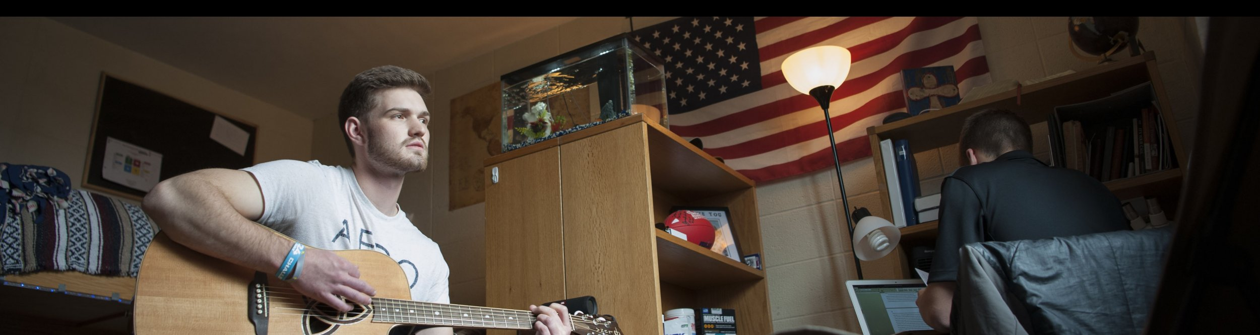 A male student holding a guitar sits in his dorm room.