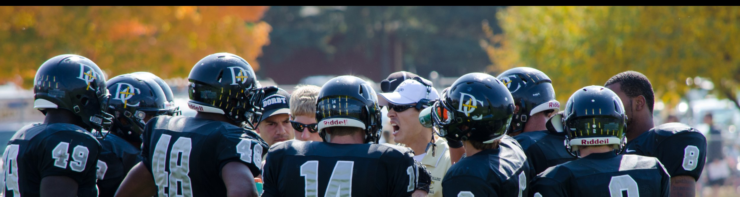 Dordt football players listen to their coach.