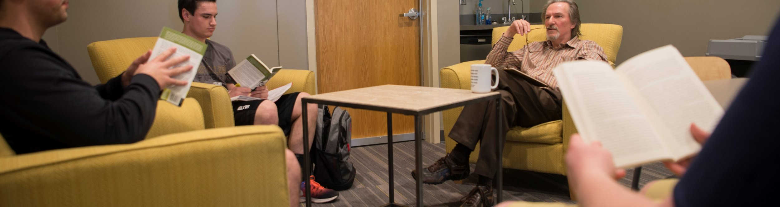 A philosophy professor speaks with three students.