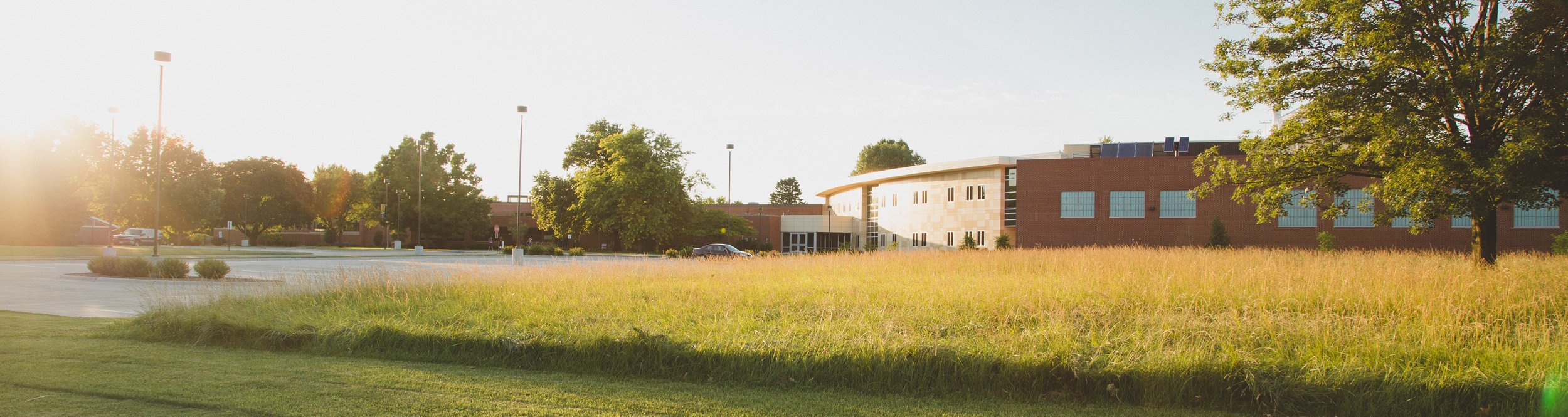 A large brick science building behind green grass.