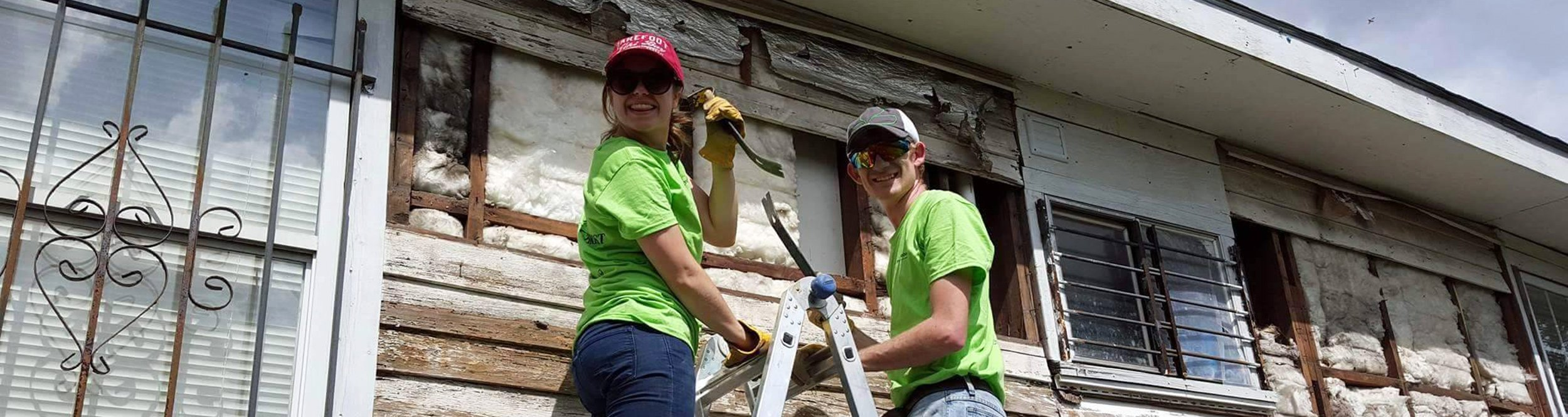 Two students, standing on a ladder, work on the dilapidated side of a house.