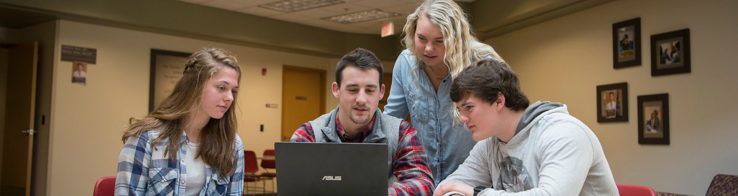 A group of students gathered around a computer.