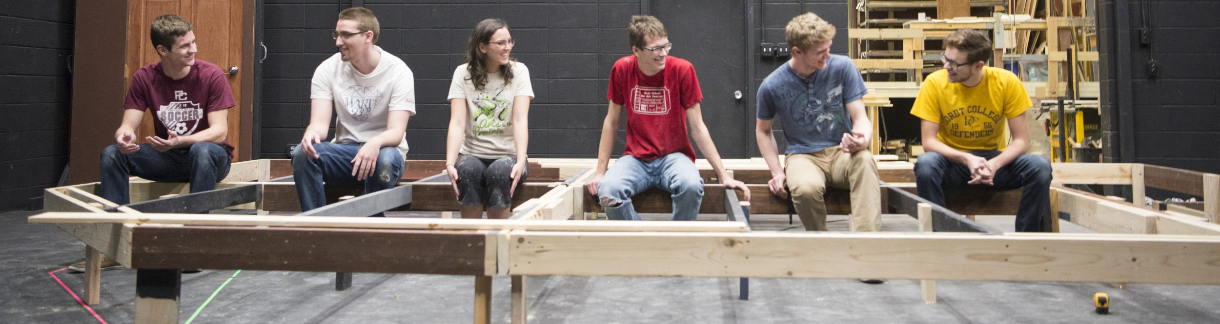 Theatre students sit on a wooden structure.