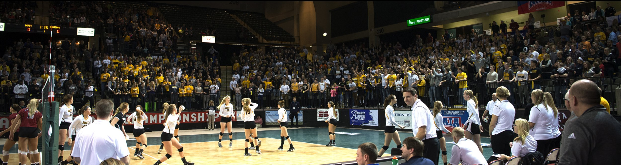 The women's volleyball team spreads out on a volleyball court surrounded by fans.