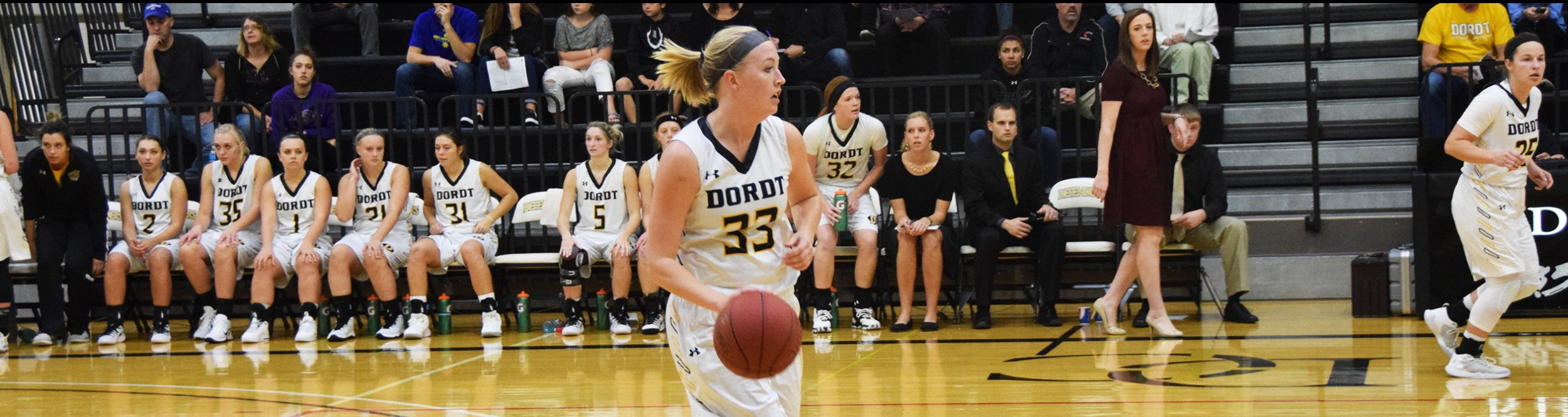 A women's basketball player dribbles the ball at Dordt.