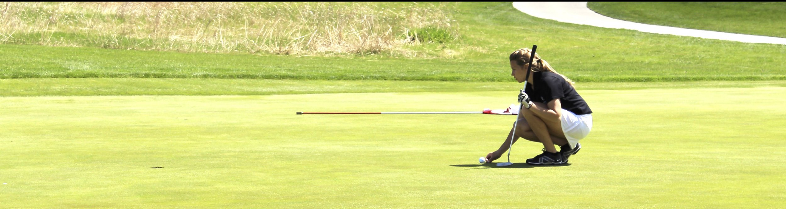 A female golfer crouches on a golf course.