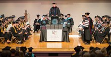 A stage of graduates being addressed by a commencement speaker.