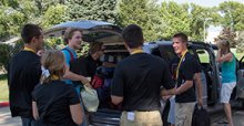 Students help to unload a van.