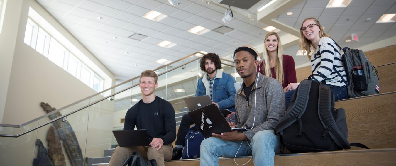 A group of students sit on steps with their laptops.