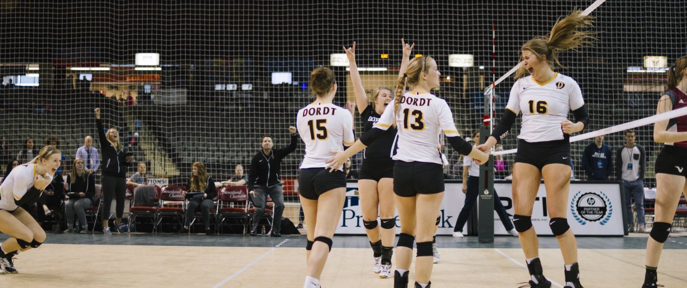 Volleyball players celebrate on the court.