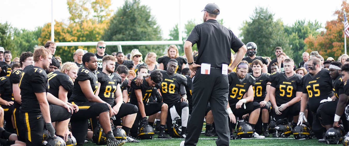 Football players kneel around a coach.