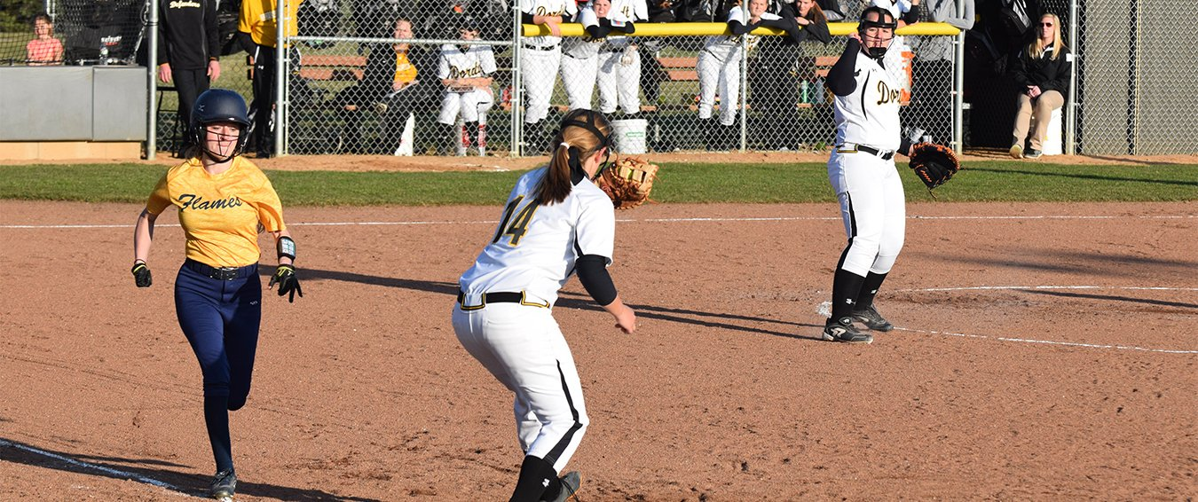 A softball player raises her glove to catch the ball.